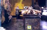 Blick in ein Geschäfts, das Schinken verkauft, Schild weist auf die Videokamera hin