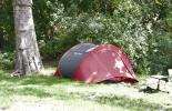 Ein Zelt am Landwehrkanal, davor ein Bürostuhl