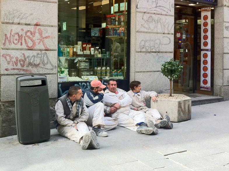 Vier Handwerker sitzen auf dem Bürgersteig