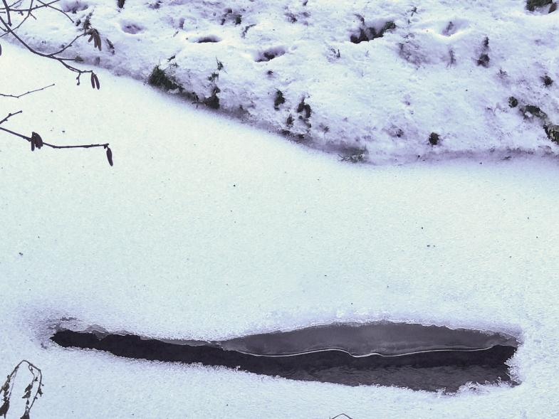 Loch im Eis im Bach