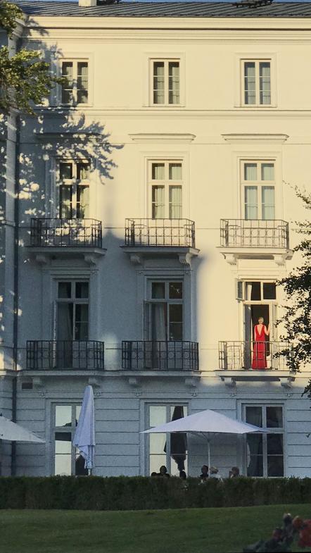 Frau in rotem Abendkleid am Hotelfenster
