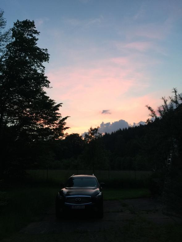 Ein Abendhimmel rückt das Auto in violettes Licht