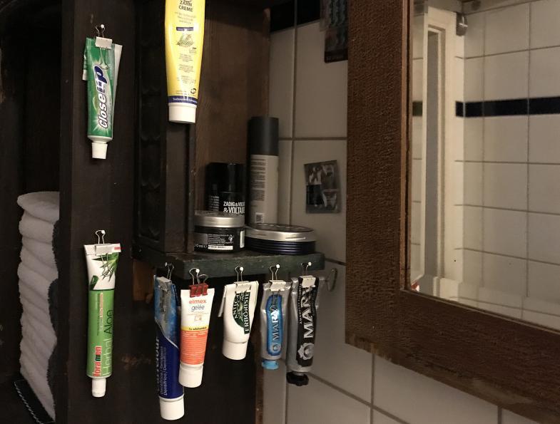im Badezimmer an Klammern aufgehängte Tuben