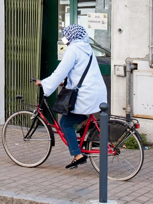 Beim Fahrradfahren wird das Handy am Ohr vom Kopftuch gehalten